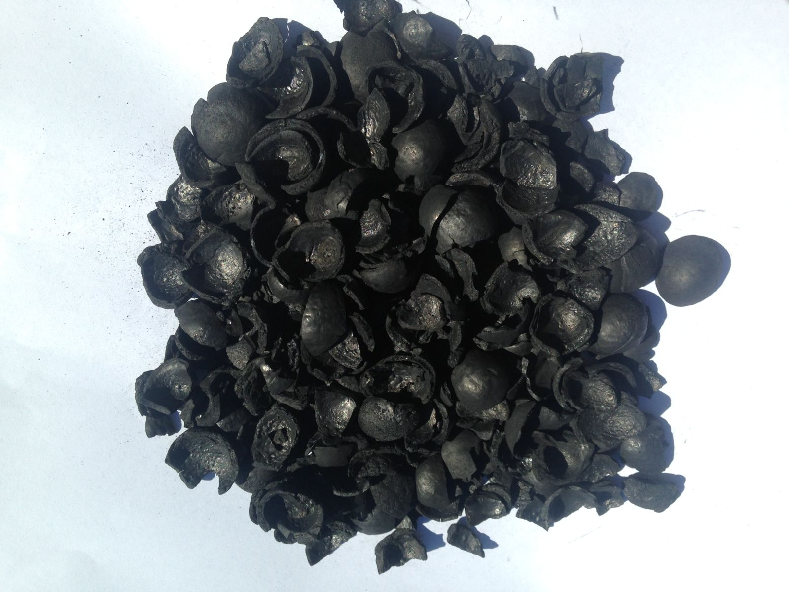 Macadamia shell biochar on white background.