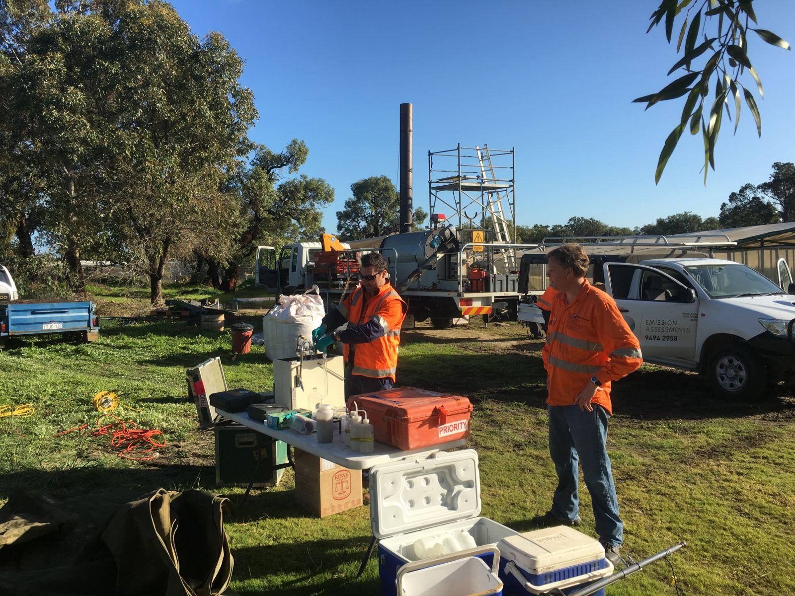 Two men setting up to conduct emissions testing on biochar kiln